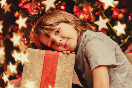 Boy with  gift box are at home decorated for Christmas. Family miracle time. Merry Christmas and Happy New Year. Imagens