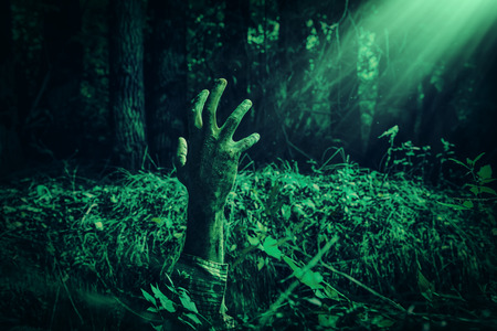 Zombie hand climbs out of the grave in the night cemetery. Halloween. Horror. 写真素材 - 130661055