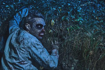 Zombie sort de la tombe dans le cimetière de nuit. Halloween. Horreur.