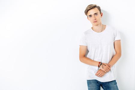 Een portret van een jonge knappe man in een wit t-shirt. Schoonheid van mannen, casual mode. Stockfoto
