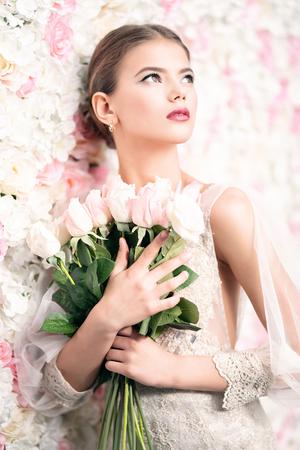 Ein Porträt einer verträumten Dame in einem Hochzeitskleid, die mit Blumen drinnen posiert. Hochzeit, Schönheit, Mode.