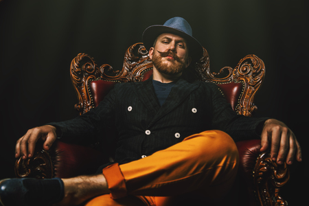 A portrait of a stylish modern man posing in the armchair. Men fashion, style.