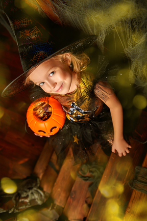Pretty little girl in a witch costume in the old wooden house with pumpkin basket. Fairy tales on Halloween. Trick or treat. Фото со стока