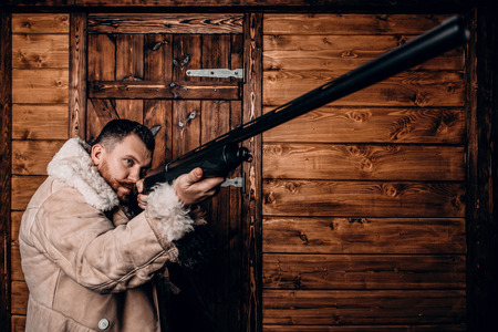 A portrait of a hunter man standing at the wooden house. Man, hunting, musket. Stok Fotoğraf