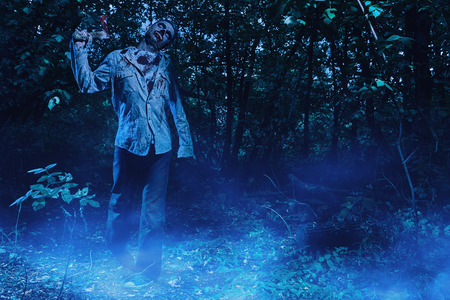 Terrible bloody zombie with an ax in his hands in the night forest. Halloween. Thriller. 写真素材 - 130844201