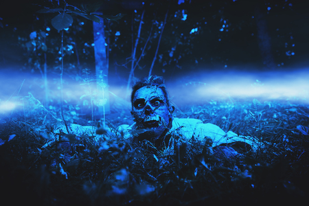 Zombie climbs out of the grave in the night cemetery. Halloween. Horror. 写真素材 - 130844632