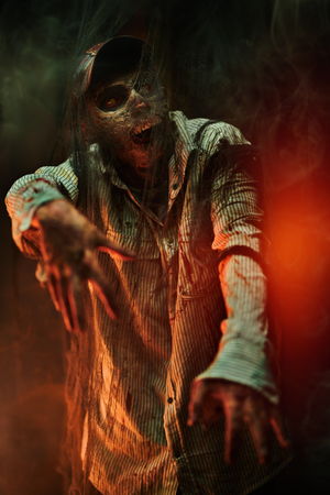 Frightening bloodied zombie in an abandoned house. Halloween. Thriller.