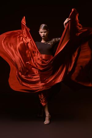 Bailarina profesional hermosa chica realiza danza latina. Pasión y expresión. Fondo negro.