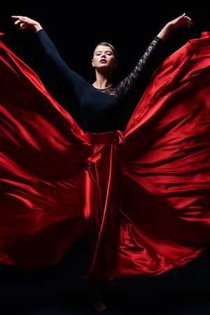 Beautiful girl professional dancer performs latino dance. Passion and expression. Black background. Stockfoto