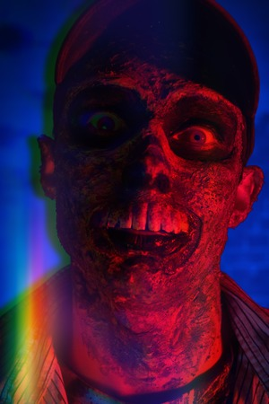 Portrait of a horrible scary zombie man in red light. Horror. Halloween.
