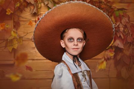 Sugar skull child boy over wooden background. Dia de los muertos. Day of The Dead. Halloween. Stock Photo