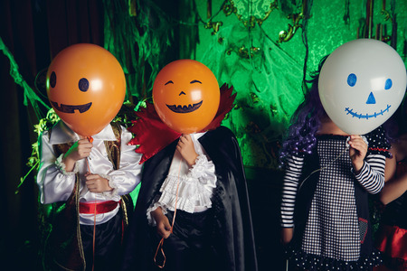 Funny children in carnival costumes with balloons on Halloween. Halloween party.