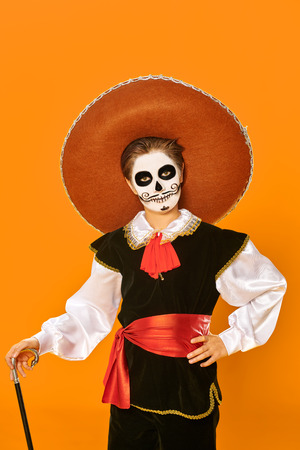 Portrait of a handsome boy with sugar skull makeup over bright yellow background. Halloween. Dia de los muertos. Day of the dead. Copy space. Stock Photo