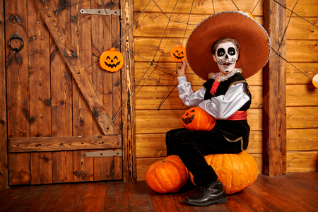 Happy excited boy with sugar skull makeup posing with pumpkins in a wooden house decoration. Halloween party. Dia de los muertos. Day of the dead.
