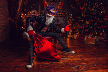 Ð¡heerful punk Santa with a bag of gifts in his hands is sitting in luxurious apartments decorated for Christmas. Bad Santa concept.