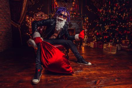 El alegre Papá Noel punk con una bolsa de regalos en sus manos está sentado en lujosos apartamentos decorados para Navidad. Mal concepto de Santa.