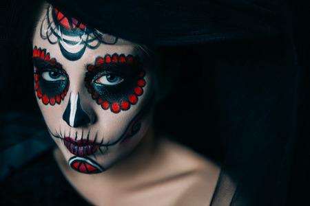 Portrait of a girl with sugar skull makeup over black background. Calavera Catrina. Dia de los muertos. Day of The Dead. Halloween. Stock Photo