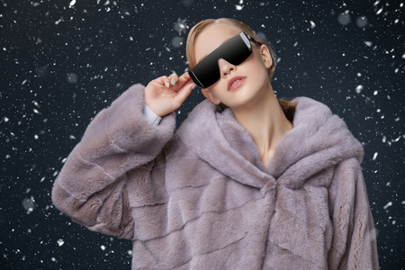 A portrait of a young fashionable woman in a fur coat with hood and sunglasses. Beauty, optics, fashion.