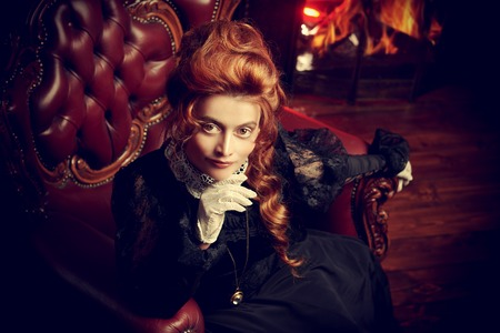The Victorian era concept. Beautiful woman in elegant historical dress and hairstyle sits in armchair in vintage interior. Baroque. Fashion. Stock fotó