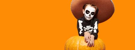 Portrait of a sugar skull child boy posing with big pumpkin over yellow background. Dia de los muertos. Day of The Dead. Halloween.