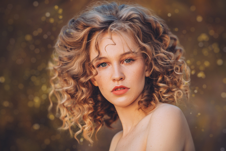 A close-up portrait of a pretty young girl with curlt hair posing outside in nature. Skincare, health, beauty.
