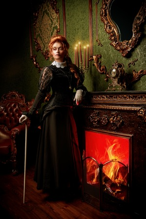 Das Konzept der viktorianischen Ära. Schöne Frau in elegantem historischem Kleid und Frisur, die im Vintage-Interieur posiert. Barock. Mode. Standard-Bild