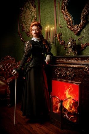 El concepto de la época victoriana. Hermosa mujer en elegante vestido histórico y peinado posando en interior vintage. Barroco. Moda. Foto de archivo