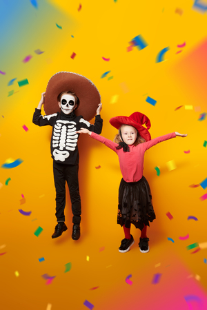 Halloween. Two happy kids in witch and skeleton costumes are jumping over yellow background. Dia de los muertos. Day of The Dead. Copy space. 스톡 콘텐츠