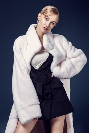 Un ritratto di una giovane donna alla moda in un cappotto di visone bianco. Bellezza, moda.