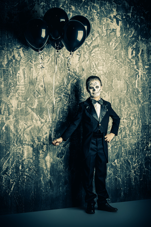 Portrait of a child boy with carnival make-up of a skeleton wearing elegant tail-coat. Studio shot over dark grunge background. Halloween. Dia de los muertos. The Day of the Dead.