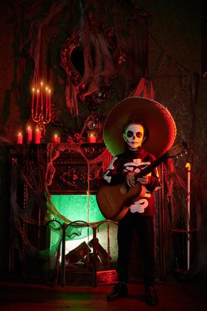 Sugar skull child boy in an old magic castle. Dia de los muertos. Day of The Dead. Halloween. Fairy tales. Children's horror stories. Stock Photo