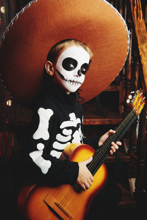 Sugar skull child boy in an old wooden house. Dia de los muertos. Day of The Dead. Halloween.