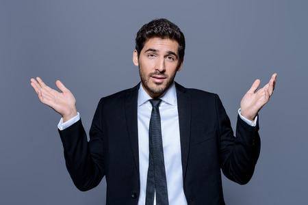 Emotional businessman pulls his hands apart, expressing surprise and disappointment. Business concept. Stockfoto