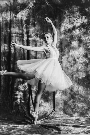 A full length monochrome portrait of an elegant refined female ballet dancer posing in the studio over the grunge background. Talent, fashion for ballet dancers. Stock Photo
