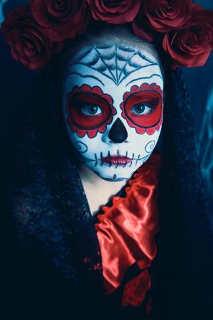 Porträt eines Kindermädchens in einem Kostüm von Calavera Catrina über Weinlesehintergrund. Kleines Mädchen mit Zuckerschädelmake-up. Halloween Party. Dia de los muertos. Tag der Toten. Standard-Bild