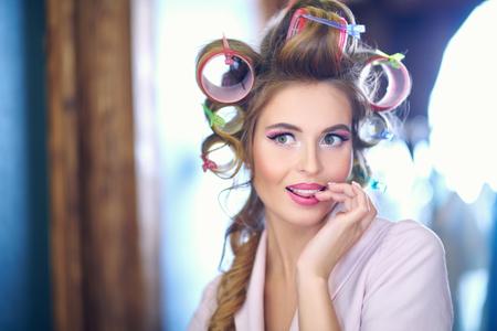 Mooie vrouw bewondert zichzelf in de spiegel. Kleedkamer, make-up artist's tafel. Schoonheid, modeconcept.