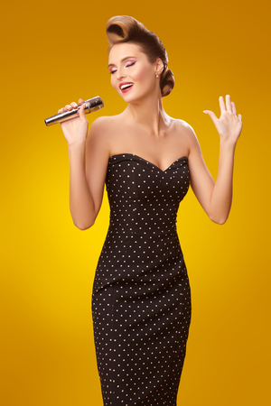 Beautiful young woman sings on a stage with a microphone in the light flashes. Pin-up style in clothes, hair and make-up.