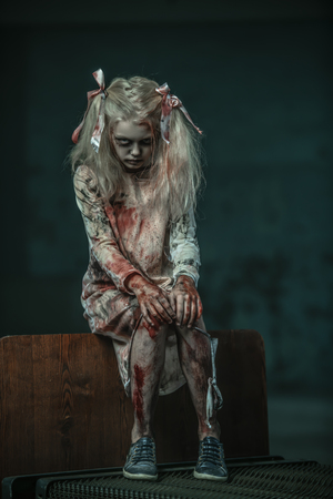 A portrait of a scary blonde zombie girl on a bed. Halloween. Horror film. 写真素材 - 131447931
