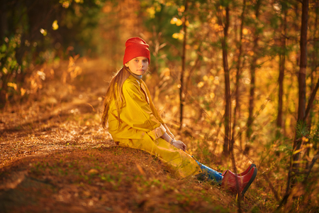 Calm dreamy girl sitting in a beautiful autumn forest, bathed in the sun. Autumn season. Stok Fotoğraf