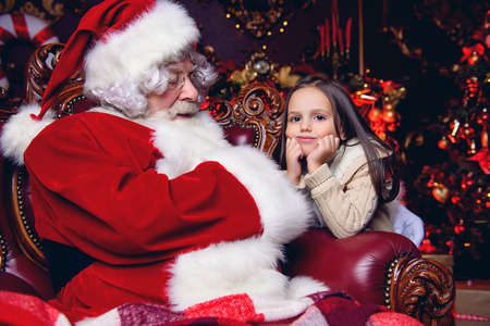 A happy young girl and Santa Claus are sitting at armchair in home. Merry Christmas and Happy New Year.