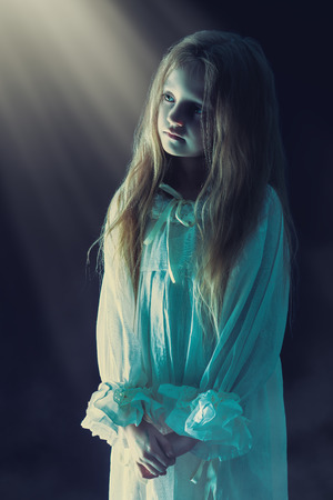 Lonely little girl in a white nightgown stands in light of heaven. Black background. Halloween.