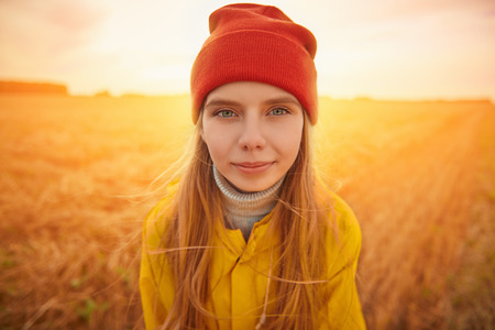 Portrait of a cute child girl in yellow raincoat and red hat standing in autumn field on a sunset.