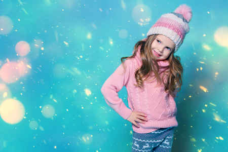 A portrait of a cute pretty girl posing in studio. Beauty, autumn and winter fashion for kids.