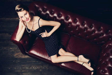 Beautiful glamorous woman with pin-up hairstyle and make-up lies on a leather sofa. Pin-up beauty and fashion concept. Stockfoto