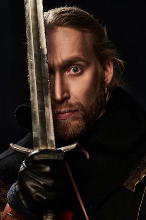 Close-up portret średniowiecznego rycerza w zbroi iz mieczem na czarnym tle. Rekonstrukcja historyczna.