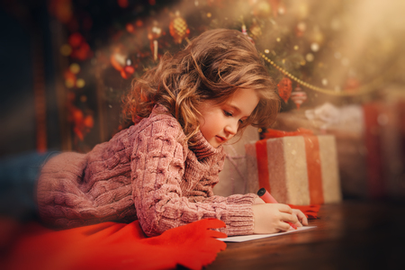A happy girl is lying in the floor in the room decorated for Christmas and writing a wish letter to Santa. Christmas, New Year. Stok Fotoğraf
