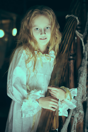 Der Geist des kleinen Mädchens in einem Nachthemd wandert nachts durch das alte Haus. Halloween.
