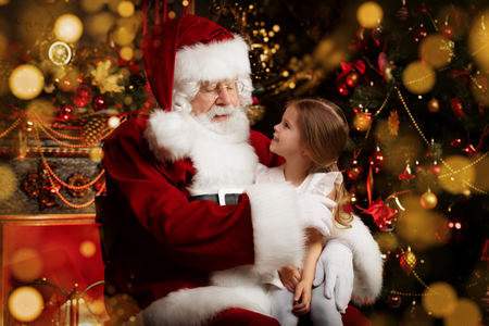 A happy young girl is near Santa Claus at home. Merry Christmas and Happy New Year.