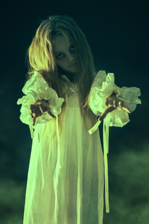 Scary little girl ghost in a white nightgown holds out her hands forward. Black background. Halloween.