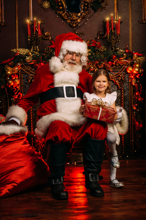 Santa Claus  and  little girl are sitting in the armchair at home with a gift bag. Merry Christmas and Happy New Year. Miracle time.